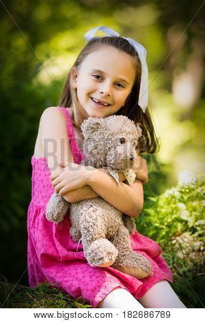 Pretty smiling little girl holding teddy bear