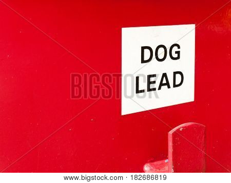 A White And Red Sign Saying Dog Lead On A Red Bin Box For Litter