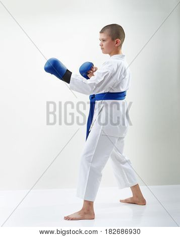 Karateka boy with blue overlays on the hands is in the rack karate