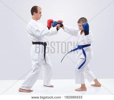 Karateka boy is training blows on overlays trainer