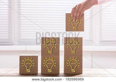 Woman's Hand Holding A Block With Light Bulb To Complete Growth Bar Graph On Desk