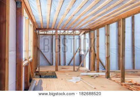 Frame construction of a wooden house using a vapor barrier. Inside view selective focus.
