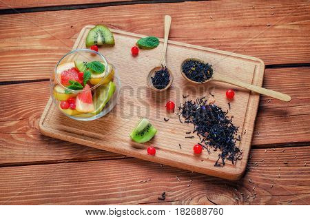 Black Tea With Herbs In Wooden Spoons  On A Wooden Board Decorated  With Kiwi, Leaf Of Mint, Banana,
