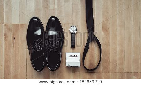 Close up of modern groom accessories. wedding rings, black necktie, leather shoes and watch on the wooden floor. Selective focus.