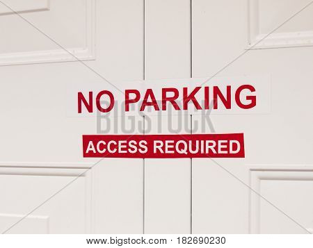A White And Red No Paring Access Required Sticker Sign Attached To Outside Garage Door Restriction E