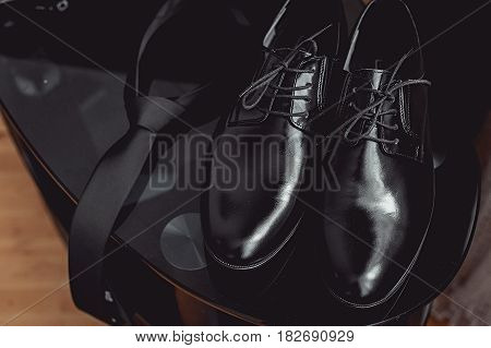 Close up of modern man accessories. black necktie and leather shoes on the black glass table.