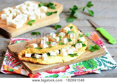 Home omelette stuffed with tofu cubes and fresh parsley on a wooden board. Delicious healthy breakfast omelette for whole family. Rustic style. Closeup