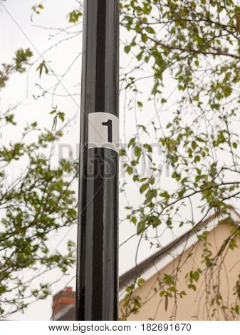A Black Pole Leading Up With A White Sticker And The Number 1 On It, Clear Directions Numbering One,