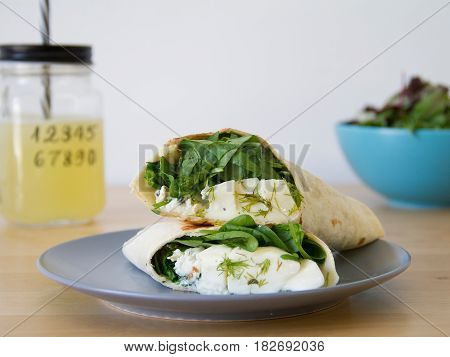 combinación de ensalada, wrap de queso feta y espinacas y zumo de limón y menta