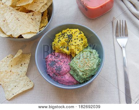 Hummus de tres colores con xips de maiz: cúrcuma, remolacha, menta. Three-color hummus with corn chips: turmeric, beets, mint.