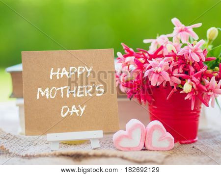 mother's day concept. Poster mock up template with flower bouquet marshmallow in the shape of heart and books over green background with Happy mother's day text