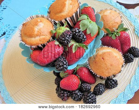 Fresh baked muffins with blueberries and strawberries