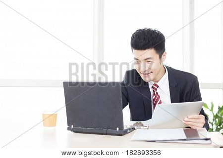 handsome chinese young businessman working with computer in modern office