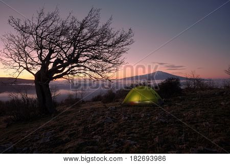 dawning on lighting tent under leafless tree and over low clouds, on background Mount Etna view from Nebrodi Park, Sicily