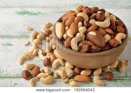 Mix of different nuts in a wooden bowl on a white background