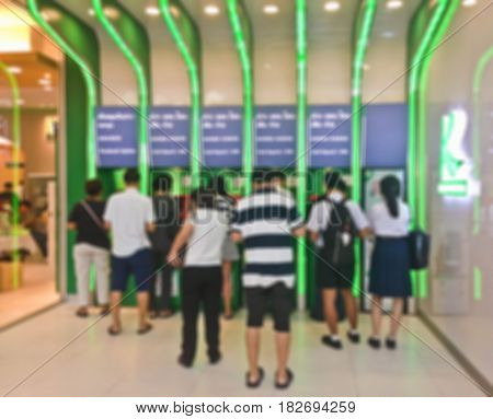 Blur or Defocus Background of People line up to use Banking Machine or ATM(Automatic Teller Machine) to Deposit, Withdraw and Transfer Money.
