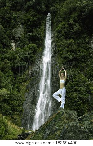 Pacific Islander woman doing yoga near waterfall