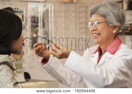 Chinese optician fitting eyeglasses on customer