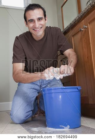 Hispanic man cleaning bathroom floor