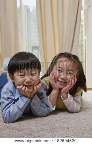 Korean boy and girl laying on the floor smiling