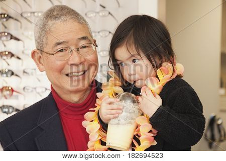 Chinese man holding granddaughter