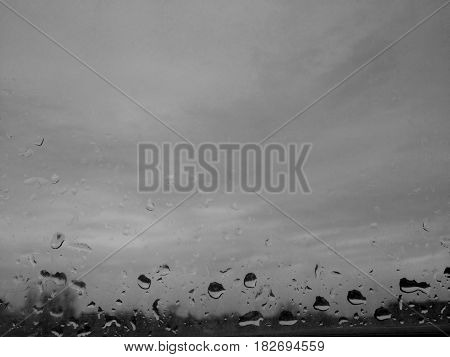 Drops of oblique rain on a windowpane on a gray sky background