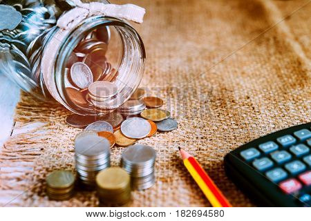 many coins in bottle place on hemp sack with calculator and pencil