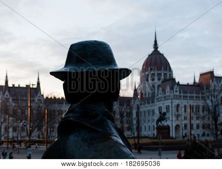 Budapest, Hungary - March 09, 2017: Back view of statue of Imre Nagy and hungarian parliament and square in the distance on sunset