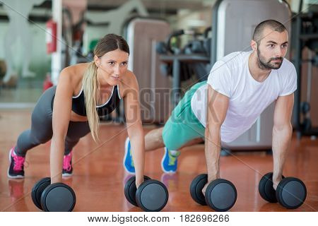 Gym man and woman push-up strength pushup with dumbbell in a workout.
