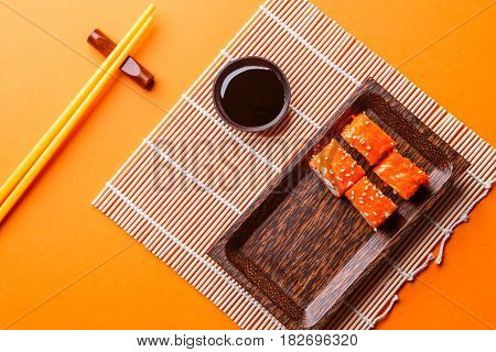 Photo of rolls on plate at table with sticks