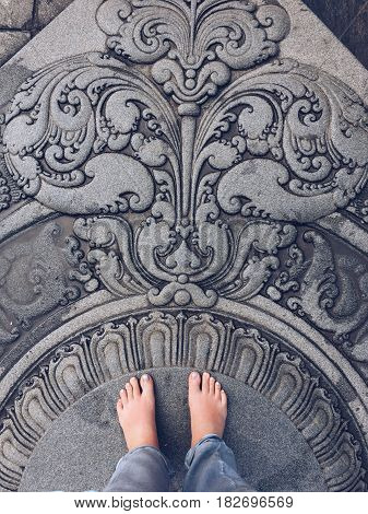 On a stone floor with a beautiful pattern bare feet female feet
