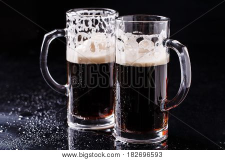 Two mugs of frothy beer on black background