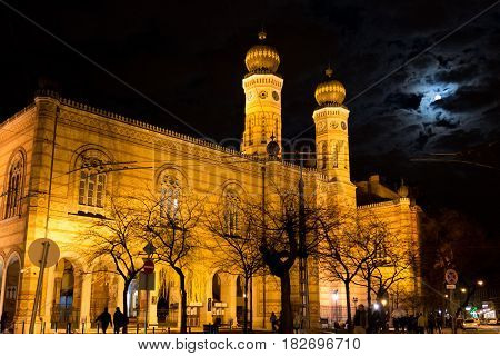 Budapest, Hungary - March 11, 2017: Illuminated Great Synagogue on Dohany Street at night with full moon behind the clouds