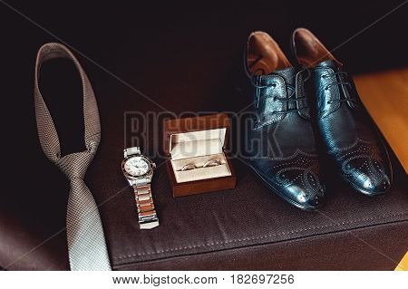 Close up of modern groom accessories. wedding rings in a brown wooden box, necktie, leather shoes and watch on a brown sofa. Selective focus.