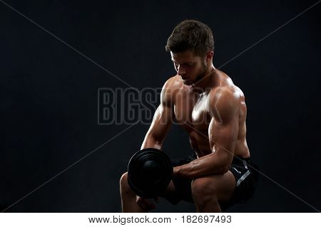 Horizontal studio shot of a shirtless muscular athletic young man pumping iron lifting weights on black background copyspace fitness gym sports muscles strengthening power masculinity hot sexy health.