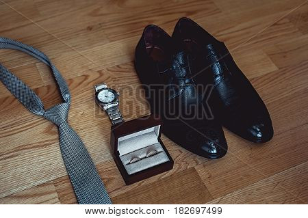 Close up of modern groom accessories. wedding rings, gray necktie, leather shoes and watch on the wooden floor. Selective focus.