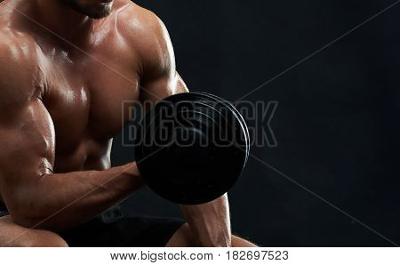 Cropped close up shot of a muscular man with strong sexy hot ripped body working out with dumbbell on black background copyspace gym fitness sportsman sportive bodybuilding nutrition diet concept.