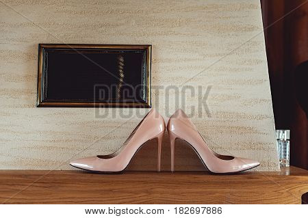 Beautiful beige wedding shoes with high heels on a wooden shelf, preparing for the wedding, details.