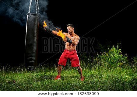 Young handsome muscular man wearing burning boxing gloves punching a heavy sandbag working out at night outdoors copyspace sport fitness martial combat fighting fighter strength effort energy.