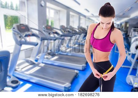 weightloss concept - beautiful slim sporty woman with measure tape in modern gym