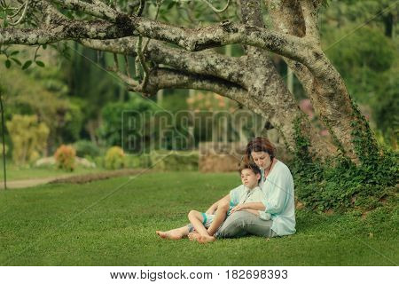 In the park under a tree on the grass sit mother and son