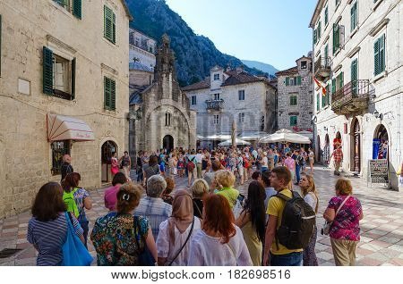 KOTOR MONTENEGRO - SEPTEMBER 22 2015: Group of tourists is located near church of St. Luke on square of Old Town Kotor Montenegro