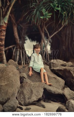 under a tree with thick roots to the boy sitting