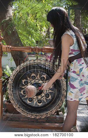 Asian woman banging gong