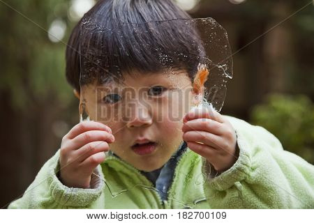 Korean boy holding sheet of ice
