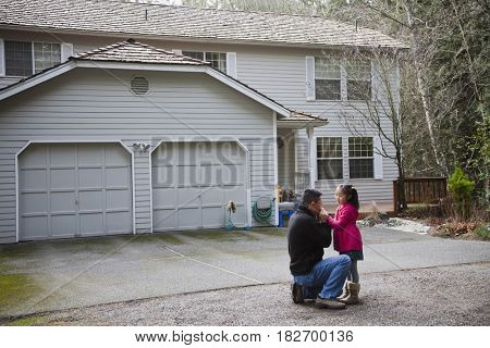 Korean father talking to daughter in driveway