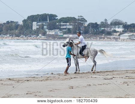 Instructor Trains A Young Man To Ride A Horse