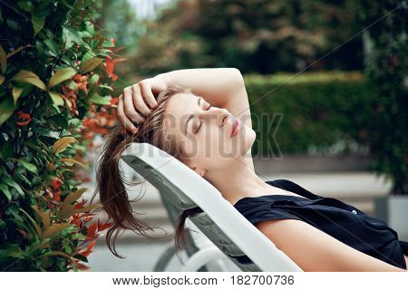 Pretty woman relaxing on a lounger outdoors
