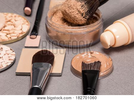 Basic makeup products to create beautiful skin tone and complexion. Corrector, foundation, powder with brushes. Shallow depth of field