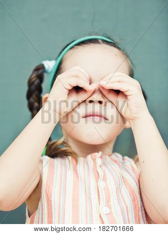 Girl looking into an imaginary binoculars. Mixed race